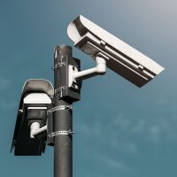 CCTV camera, modern era anti-terrorist electronic surveillance security cameras against blue sky that symbolizes freedom
